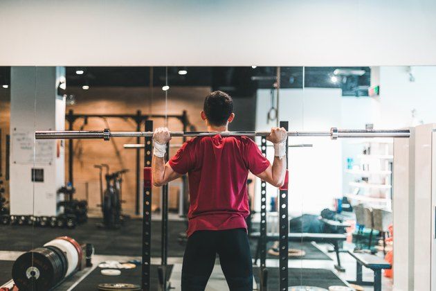 rear view of man using barbell to do a good morning exercise