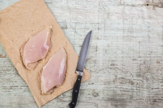 Chicken breast on brown paper and a knife