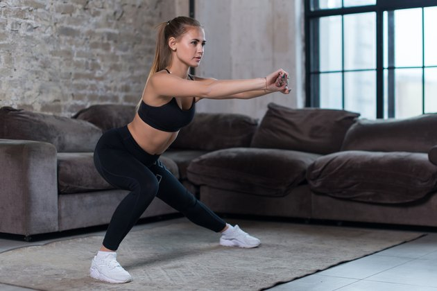 Beautiful fit girl doing home workout performing lateral lunges in a sitting room