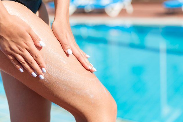 Woman applying exercise gel like Sweet Sweat cream on her leg by a swimming pool