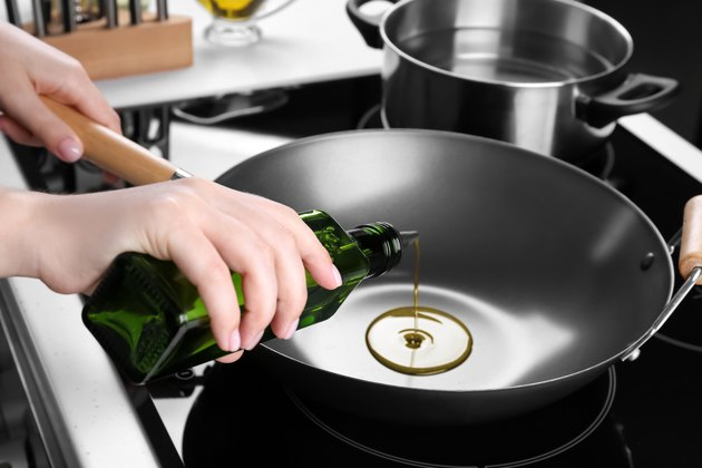 Woman pouring oil from bottle onto wok in kitchen