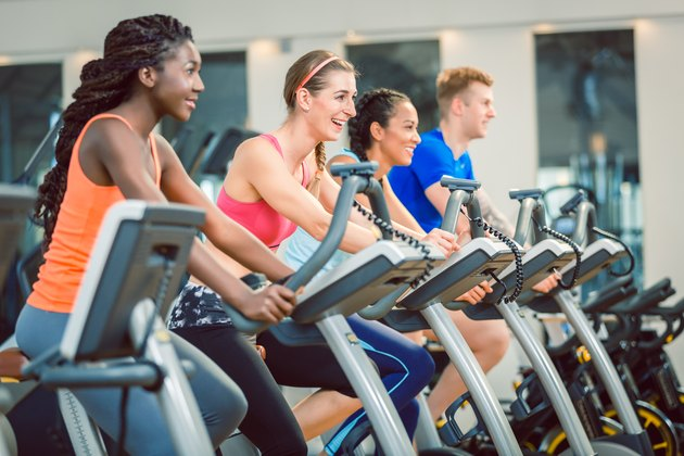 Side view of a beautiful woman smiling while cycling during exercising class at the gym