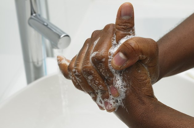 close up of Black person washing hands