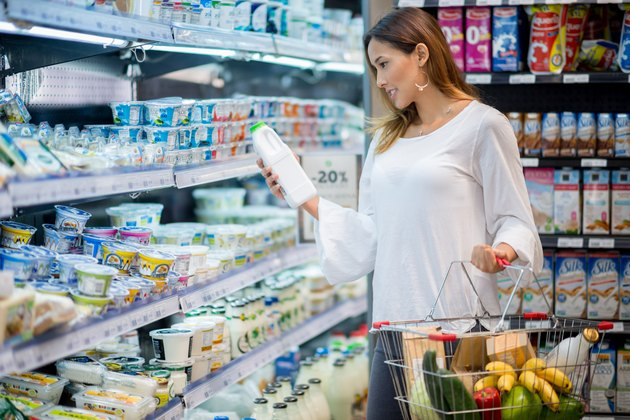 A woman in a grocery store looking at milk alternatives
