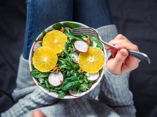 Woman in jeans at bed, holding vegan salad bowl with immune boosting foods
