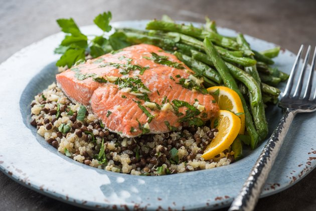 A plate of salmon over quinoa with green beans on the side
