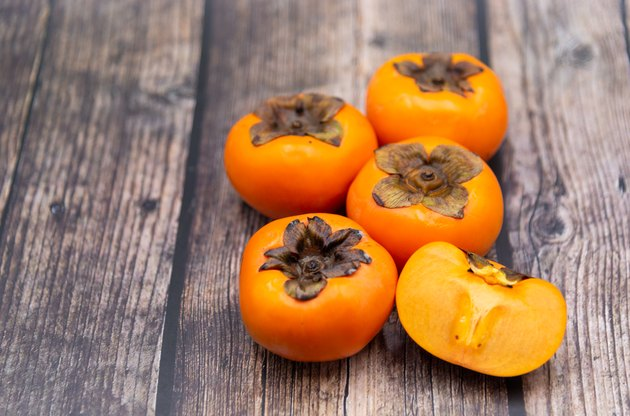 Persimmon fruit on old wooden background, Top view.