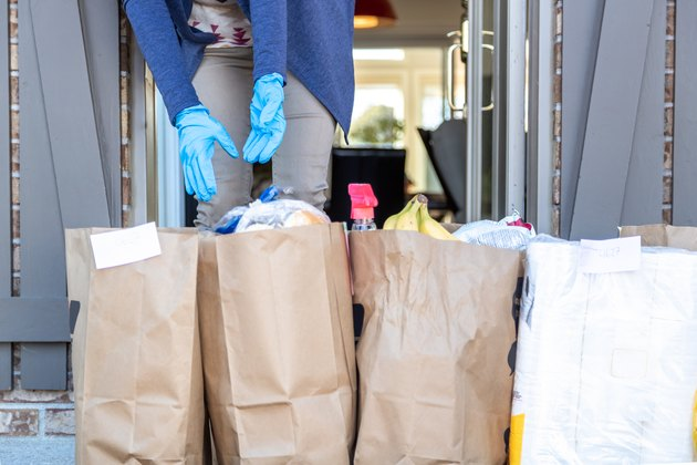 Woman taking in Grocery bags waiting outside at front door after delivery