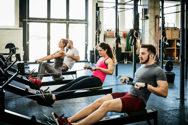 Fitness Enthusiasts Exercising Using Rowing Machines