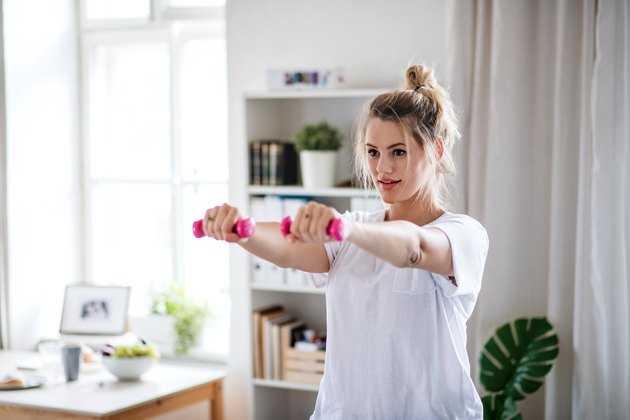 Young woman with dumbbells doing exercise in bedroom indoors at home
