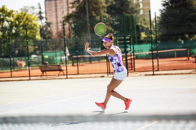 Female tennis player hits the ball with forehand .