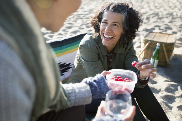 Smiling women eating raspberries at a beach picnic