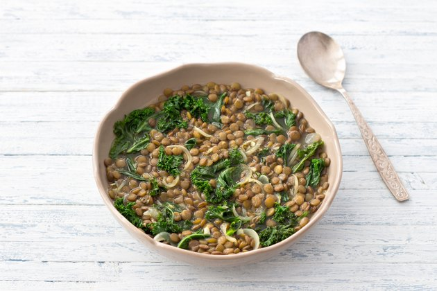 Stewed kale lentils with onions and garlic on a light background
