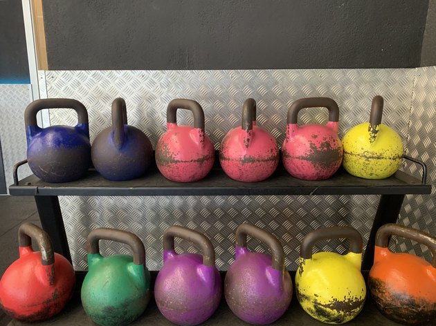 Kettlebells of different colors at the gym on rack