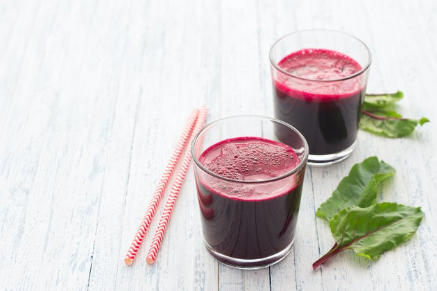 Fresh beet juice in glasses with a straw on a light blue background