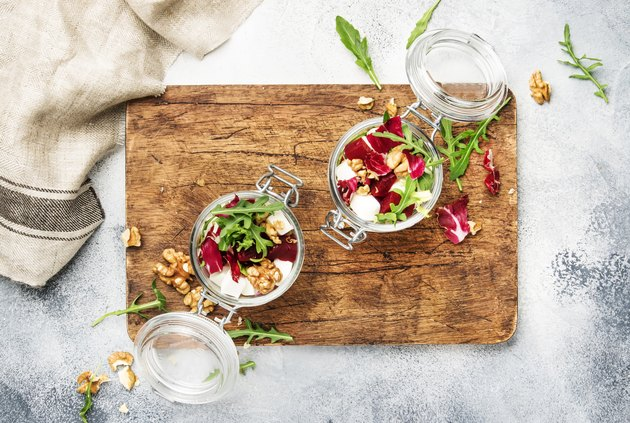 Beet salad with fresh arugula, soft goat cheese and walnuts, trendy salad jar, steel fork, gray kitchen table background, wooden cutting board, copy space, top view