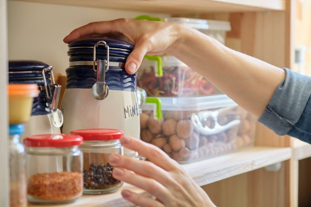 Woman in the kitchen with can of dry mint, food storage, pantry
