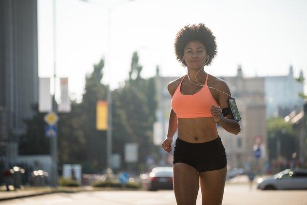 Athletic fitness girl running outdoors, enjoying music.