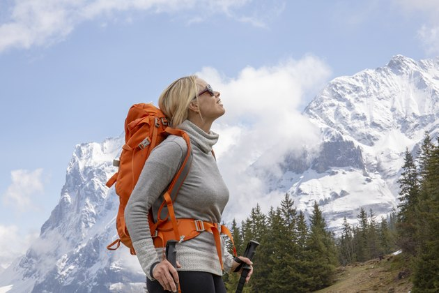 Female hiker ascends snowslope, in mountains