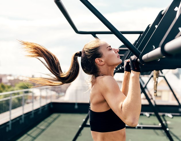 Female athlete exercising chin-ups. Side view of young woman doing workout on a roof terrace.