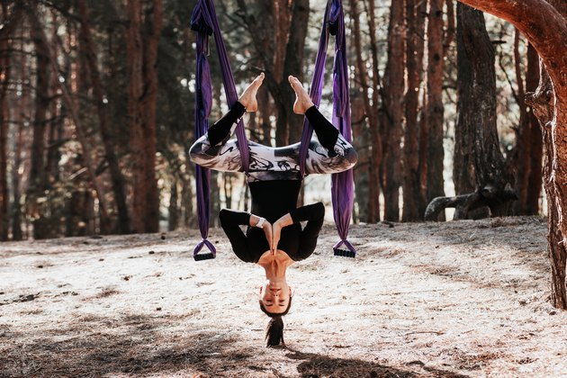 Fly yoga. Woman athlete feels satisfied and relaxed enjoying a yoga exercises in the forest