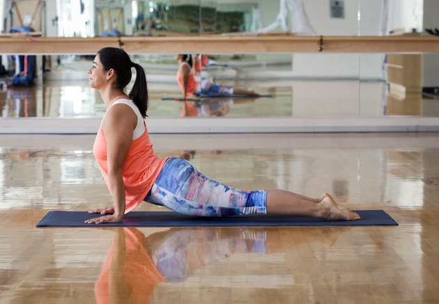 Side view of woman doing upward facing dog position while exercising in gym