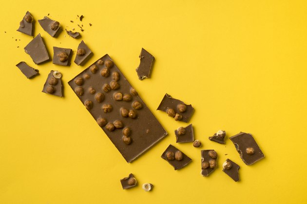 A chocolate bar with scattered pieces on a yellow background