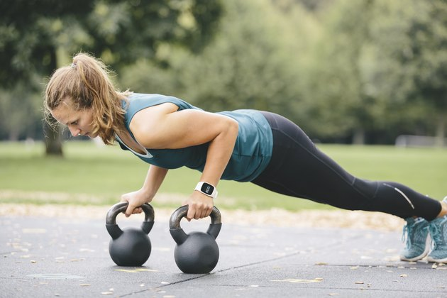 Young woman going pushups on kettlebells