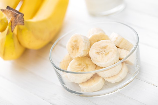 Fresh sliced bananas in a bowl on white wooden background.
