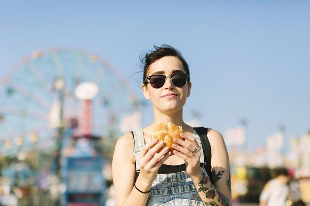 A young woman eating a hamburger at an amusement park