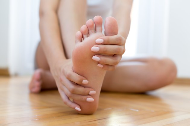 Closeup young woman feeling pain in her foot