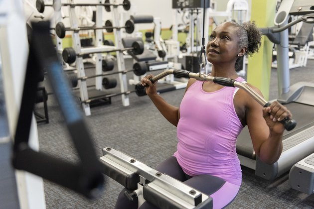 Mature woman weight training in gym