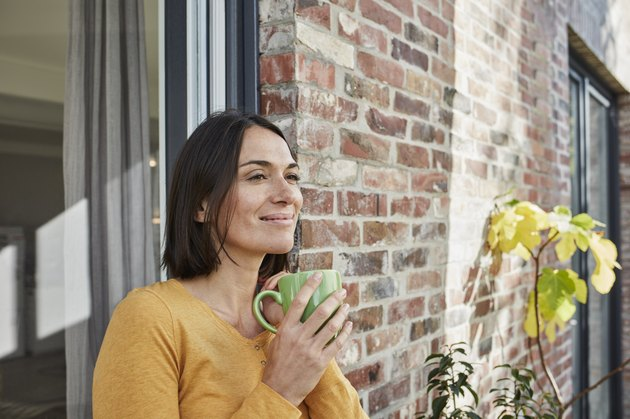 Smiling woman drinking from cup in front of her home