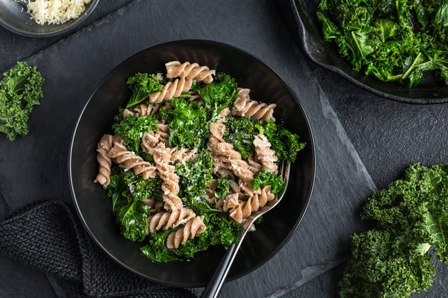 Whole grain pasta with kale in black bowl