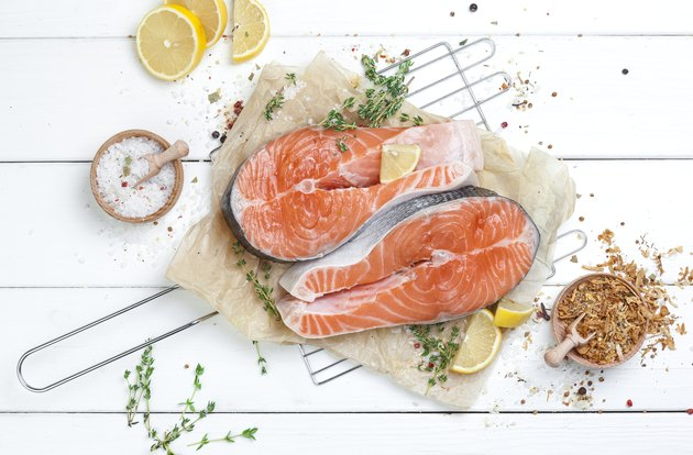 Raw salmon steak on white wooden background top view