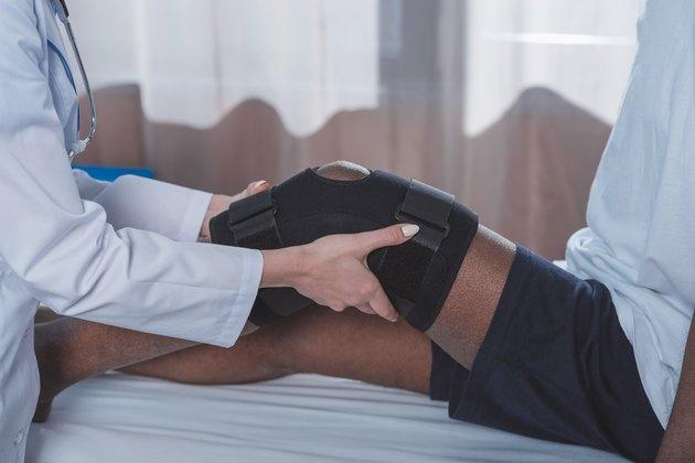 doctor putting on knee brace