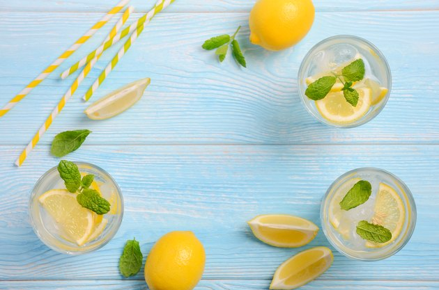Cold refreshing summer drink with lemon and mint on light blue wooden background.