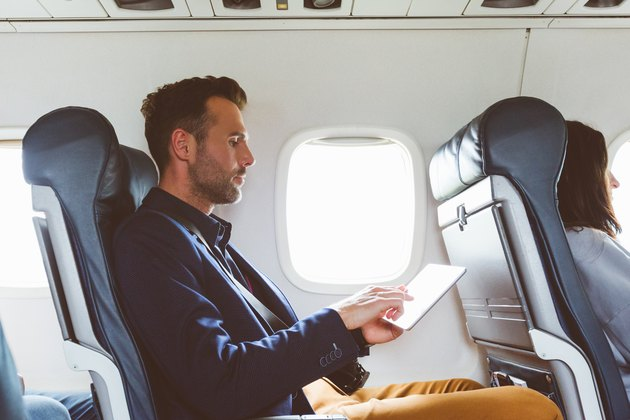 Businessman using digital tablet in airplane