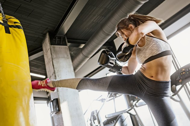Young woman training kickboxing ,high kick punch