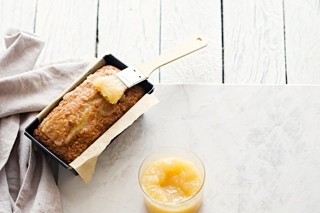 Glazed applesauce oatmeal bread on a white marble table
