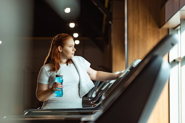 Selective focus of overweight girl with towel on shoulder holding sports bottle while standing at treadmill