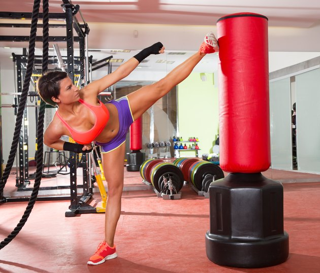 gym woman kick boxing with red punching bag