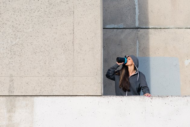 Fitness woman drinking protein shake after urban workout