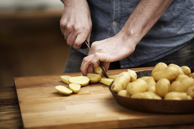 close up of man cutting potatoes on wooden cutting board