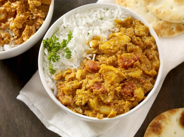 Chicken tikka masala and white rice in a bowl.