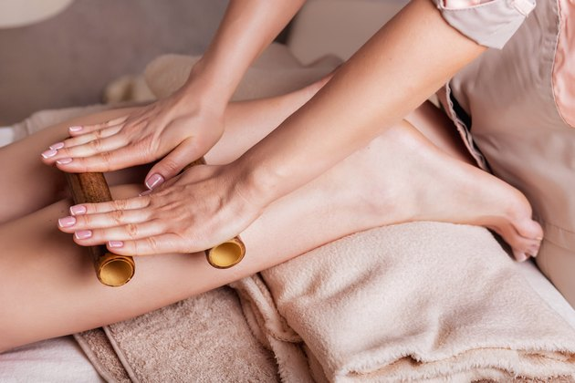 Massage of human foot in spa salon  with bamboo sticks