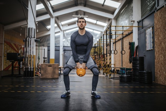 Man doing a kettlebell superset workout in the gym