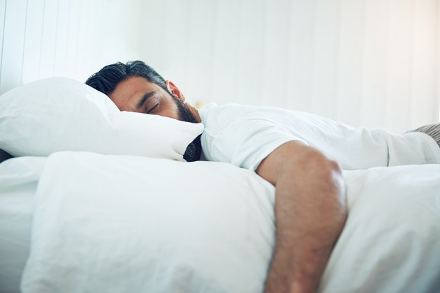 A man sleeping on his side in bed