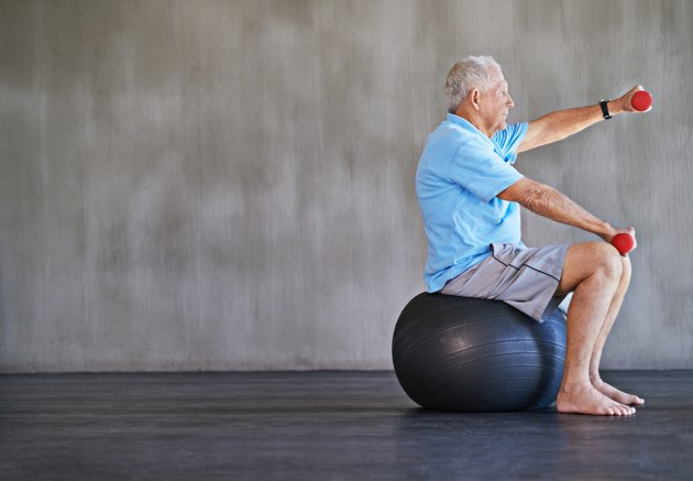 older man on stability ball doing reps and sets of dumbbell front raises