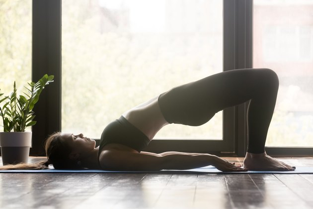 Woman doing pilates or yoga Glute Bridge pose